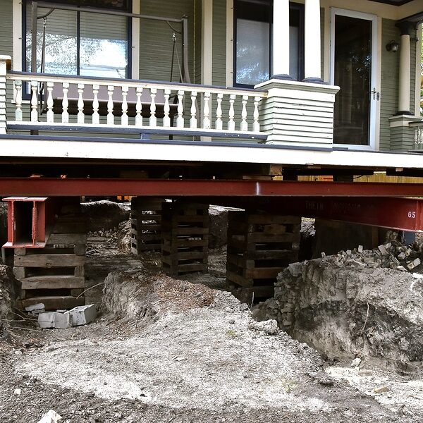an old house (exposing the porch) rests on steel girders as a new concrete basement is being created. basemen and foundation is being created